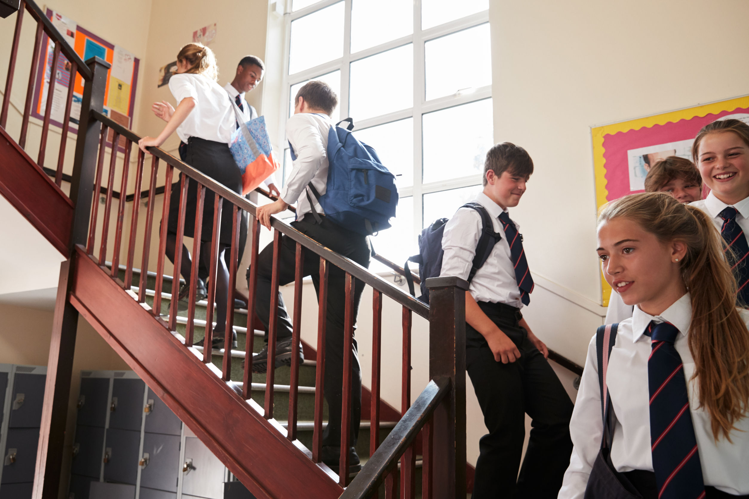Happy secondary school pupils on staircase
